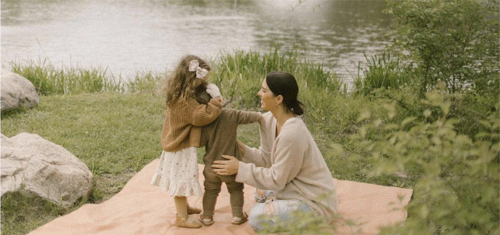 mother and daughter playing outside on leather mat
