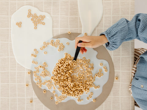 cereal bowl with spilled milk on a gathre placemat and tablecloth