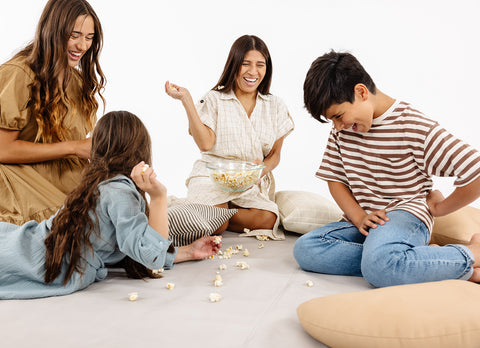 A family laughs together on floor cushions, throws popcorn