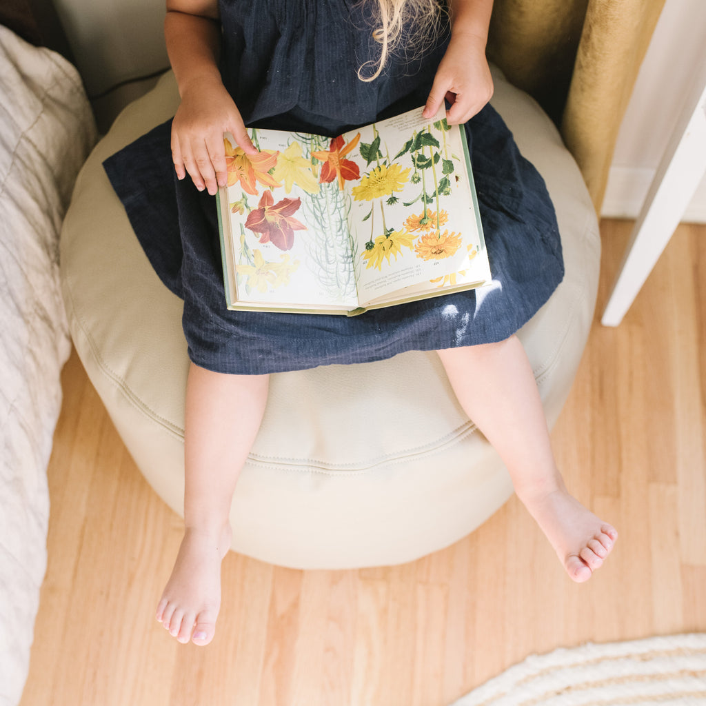 Child sitting on white pouf reading a book