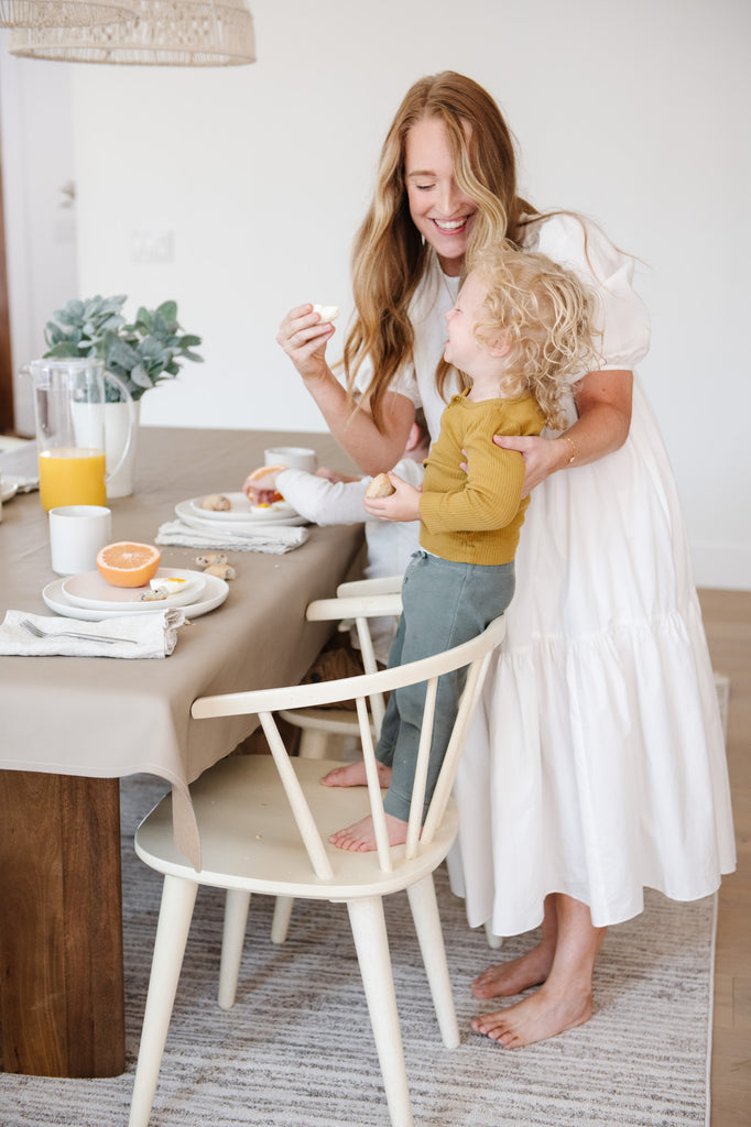 Woman feeding child at breakfast table with tablecloth