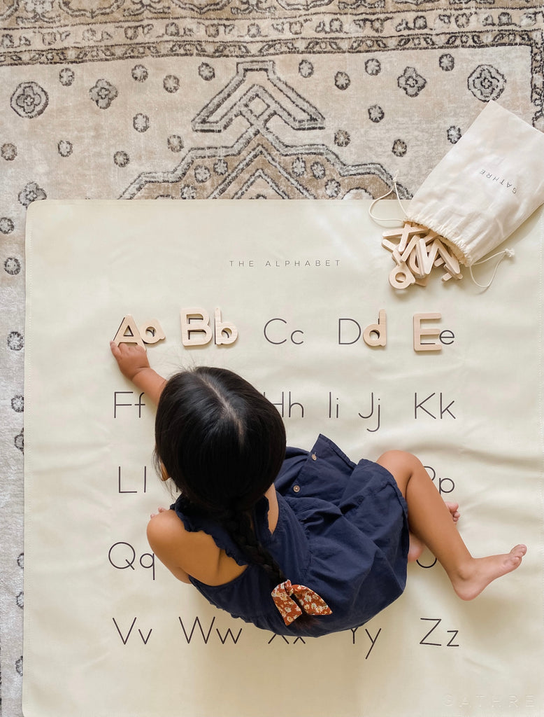 Little girl playing on alphabet mat with wooden letters