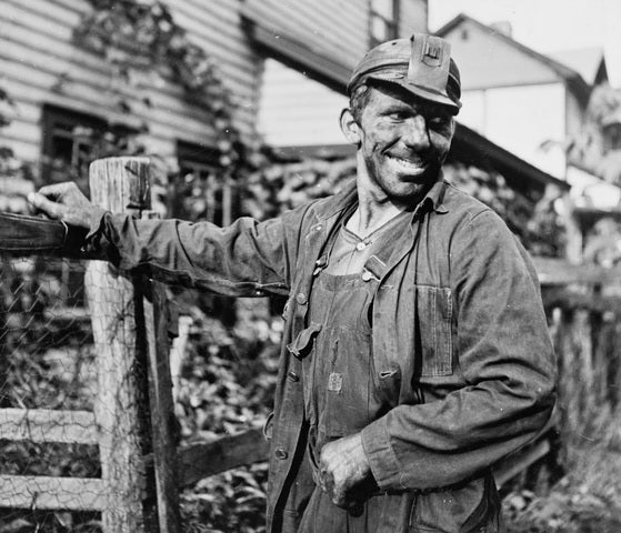 black and white photograph of man in workwear dirty