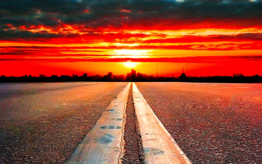 two lane road close up with red sunset centered on painted lines