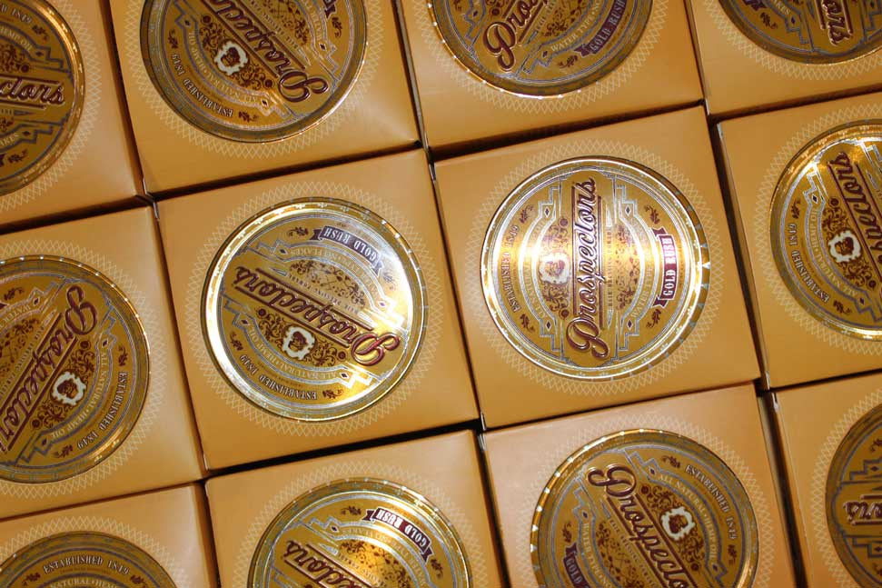 array of packaged prospectors pomade cans in cardboard boxes