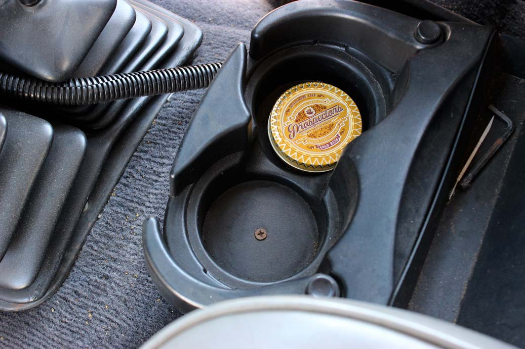 Prospectors pomade can in cup holder of car