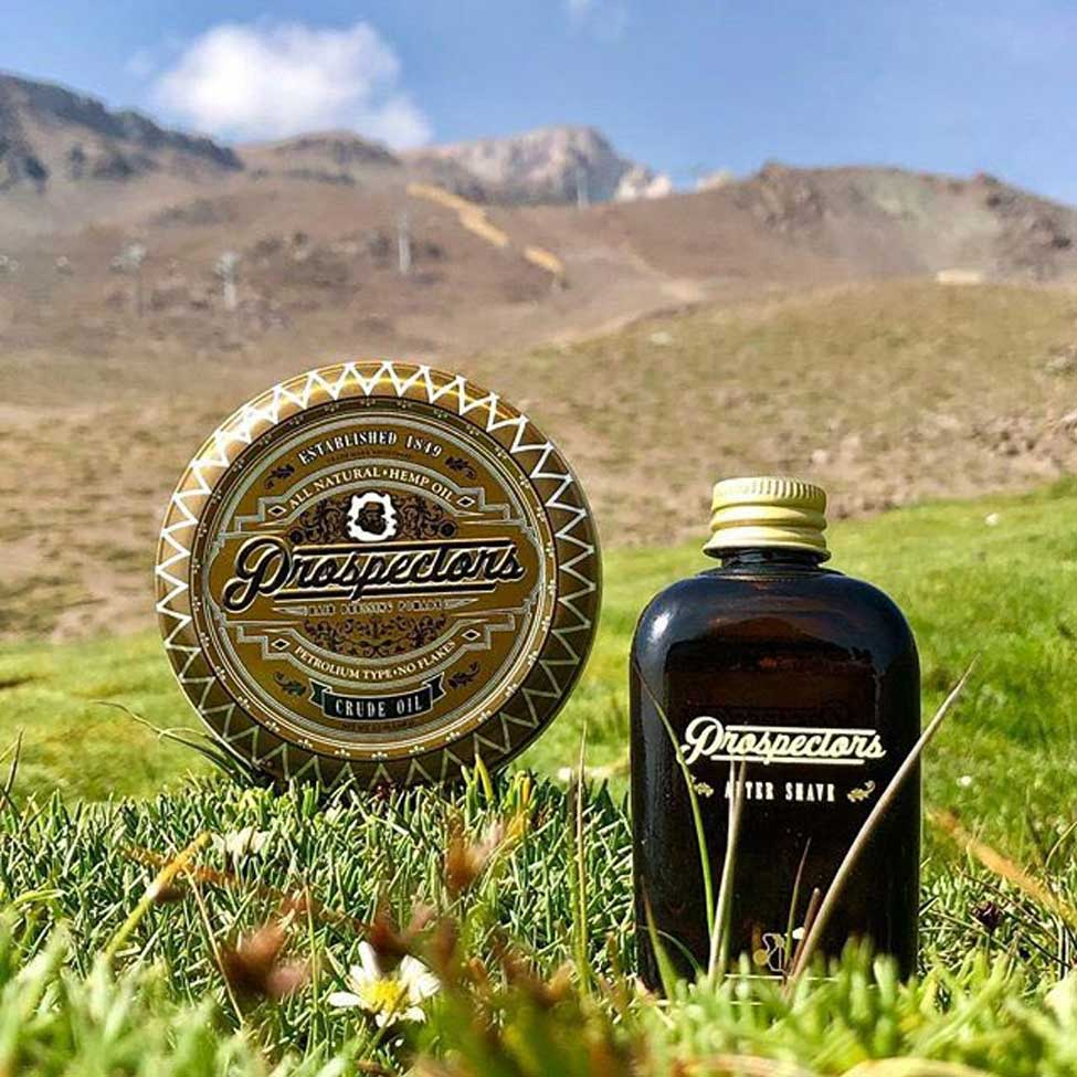 Prospectors Crude Oil Pomade and aftershave in a field next to a mountain