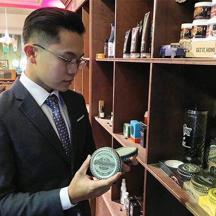 Man in suit opening up Prospectors Pomade Can near shelf