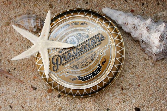 Prospectors Pomade Can at the Beach with Sand, Shells and Water