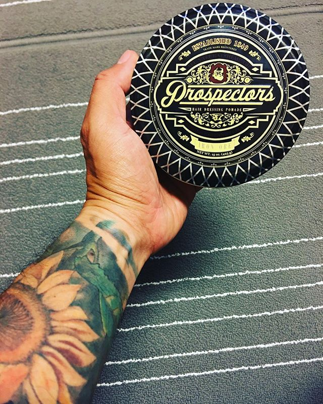 jason.cy.khoo holding a tin of prospectors pomade with tattooed arm