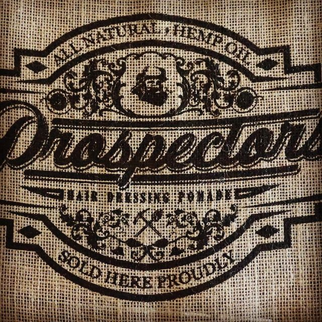 new_boy_tommi close up shot of prospectors pomade label logo in brown and tan