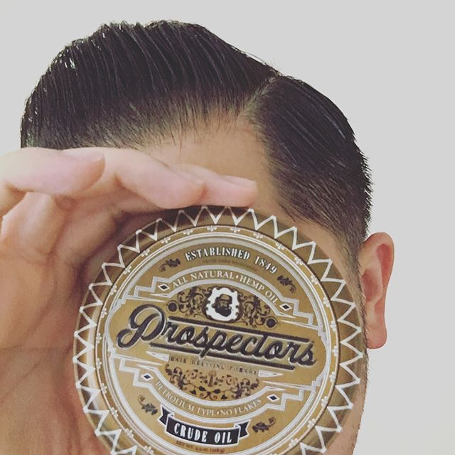 world_men_s_grooming holding a can of prospectors pomade up to the face