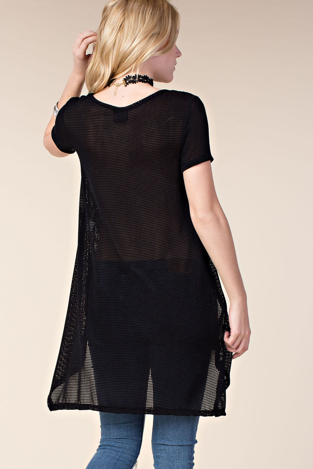 Back view young woman wearing black short sleeved high low tunic top with scattered studs
