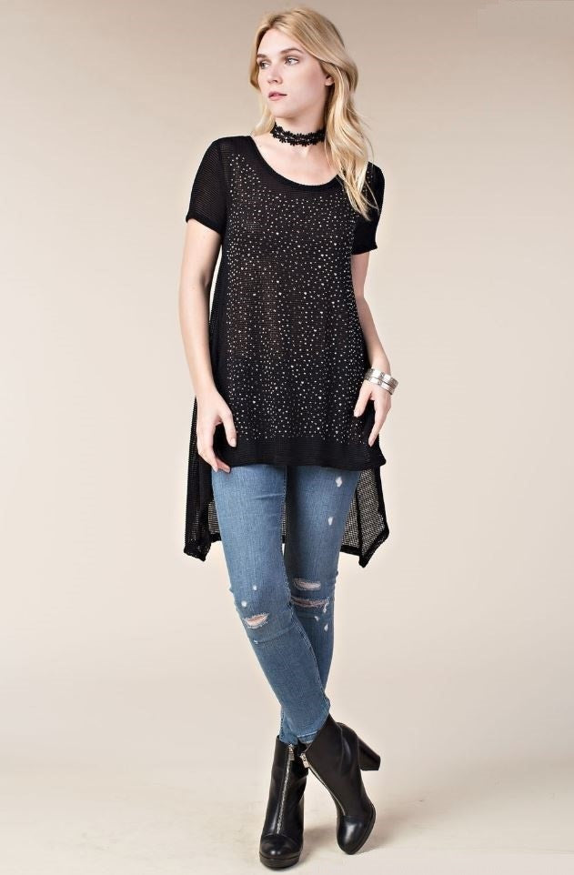 Front full view young woman wearing black short sleeved high low tunic top with scattered studs