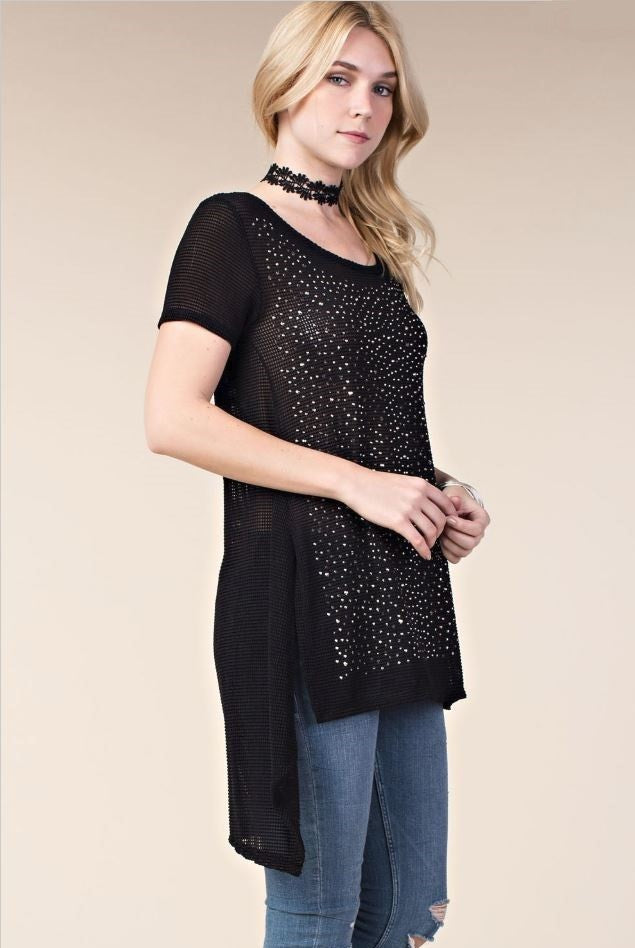 Side view young woman wearing black short sleeved high low tunic top with scattered studs