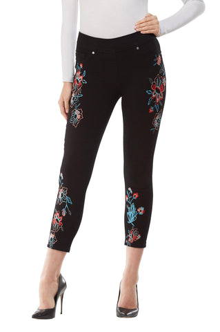 Front view woman wearing black compression cropped pants with floral embroidery