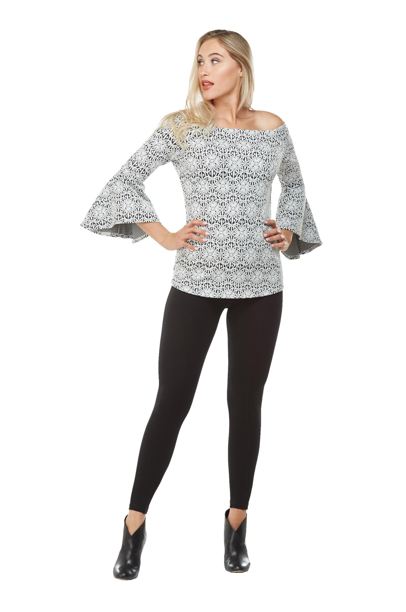 Full view woman wearing black/white off the shoulder jacquard knit  bell sleeve top