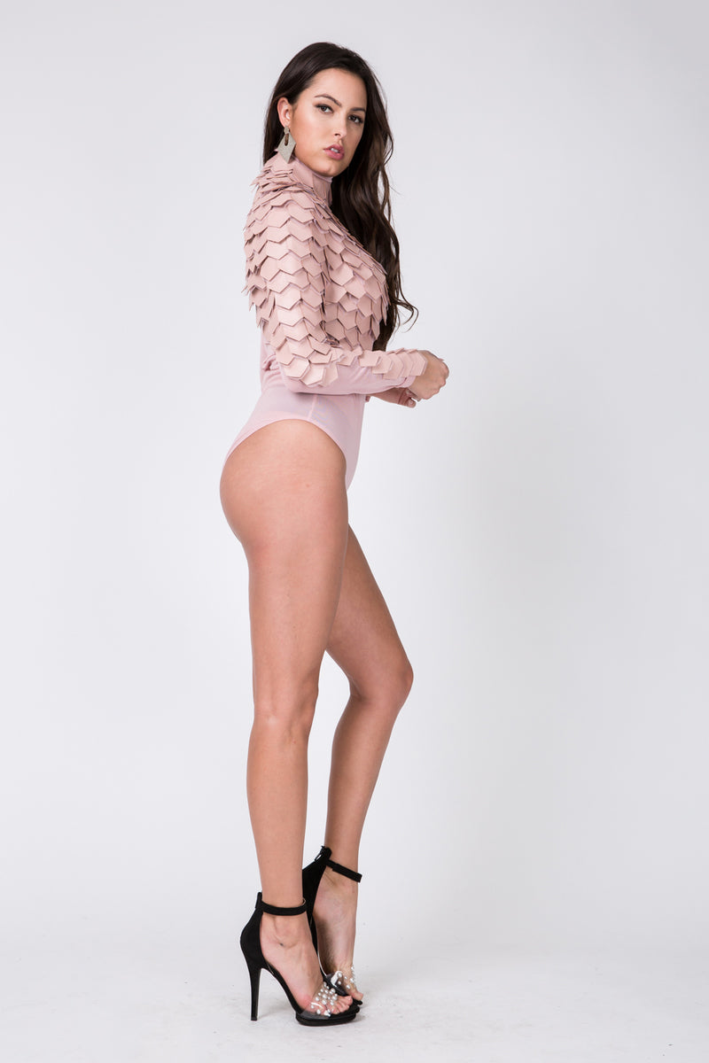Full side view young woman wearing blush pink long sleeve mesh bodysuit with pleather scales