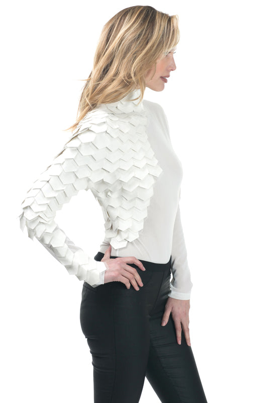 Right side view young woman wearing off white long sleeve mesh bodysuit with pleather scales