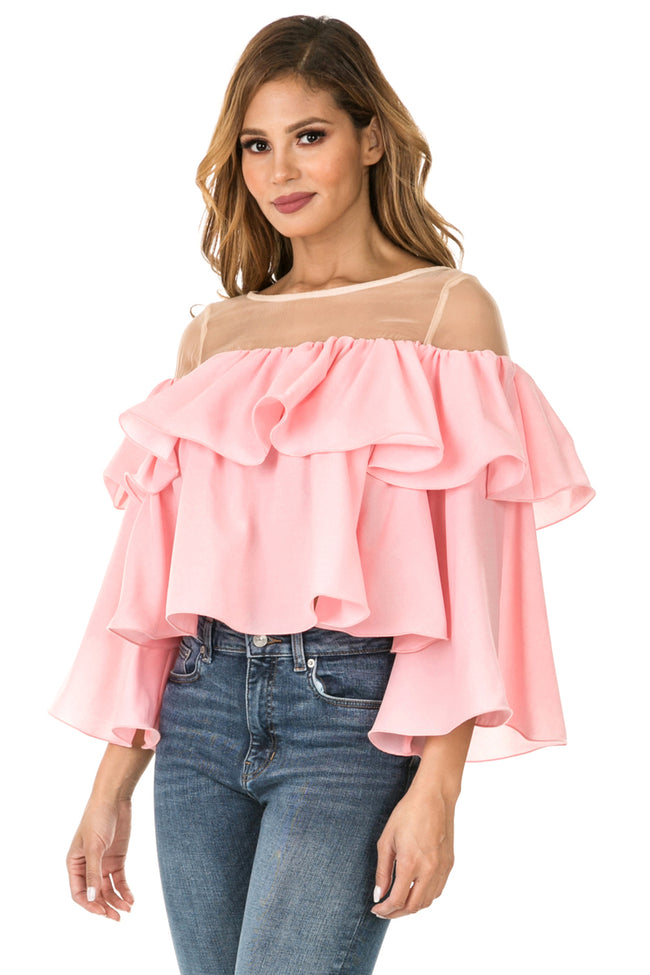 Front three quarter view woman wearing light pink sheer shoulder yoke ruffled crop blouse