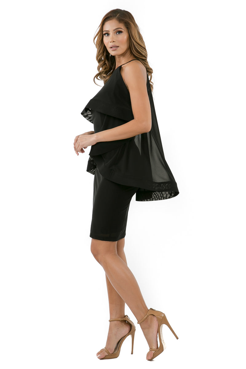 Side full view woman wearing black halter dress with layered high-low cape