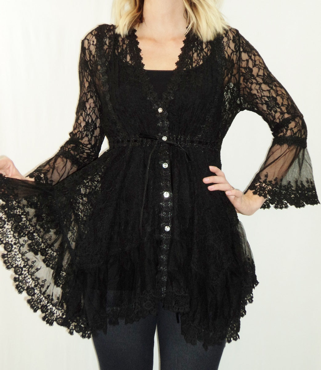 Front view woman holding out hem of black empire waist stretch lace bell sleeve tunic top