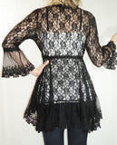 Back view woman wearing black empire waist stretch lace bell sleeve tunic top