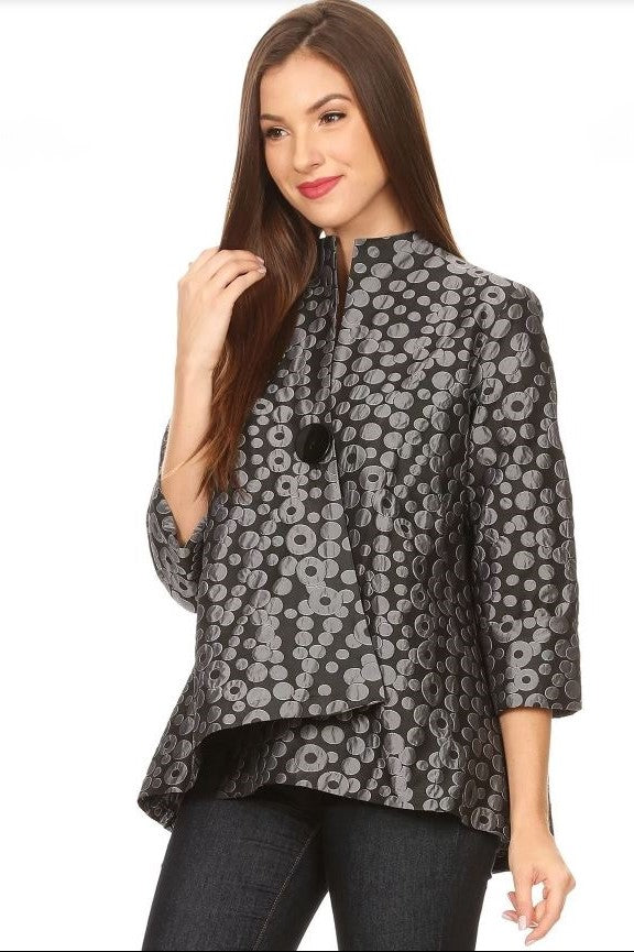 Left side view woman wearing asymmetrical grey circle jacquard jacket with black button closure