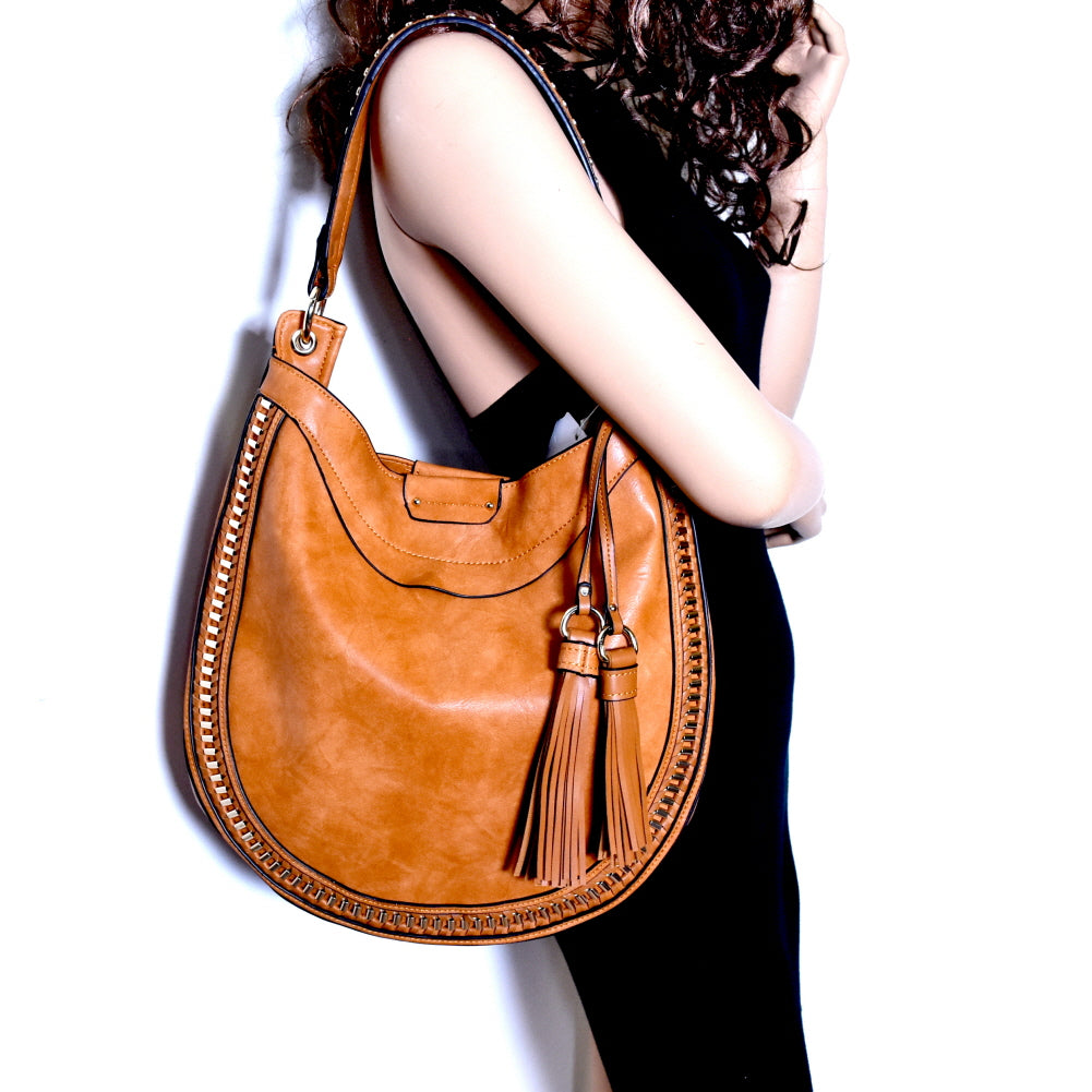 Side view tan rounded hobo handbag with two tassels on left side on the arm of a girl