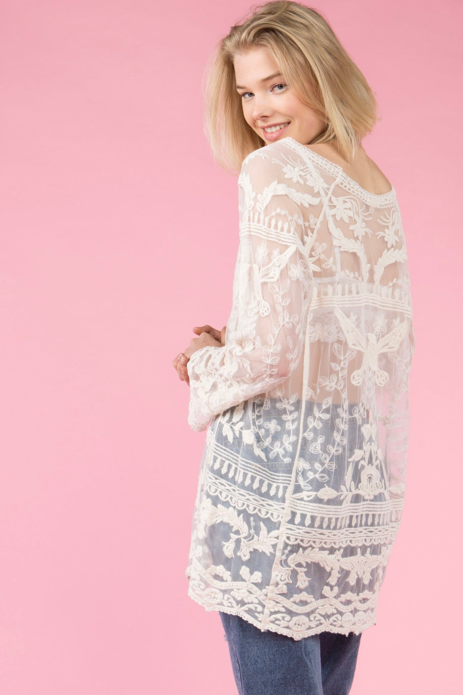 Back view young woman wearing natural colored lace tunic top with wide boat neckline