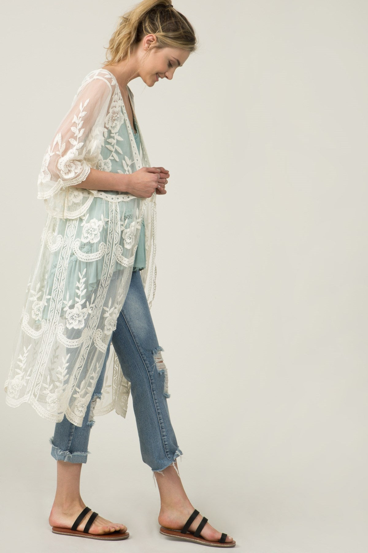 Right side view view young woman wearing sheer ivory empire waist embroidered cardigan