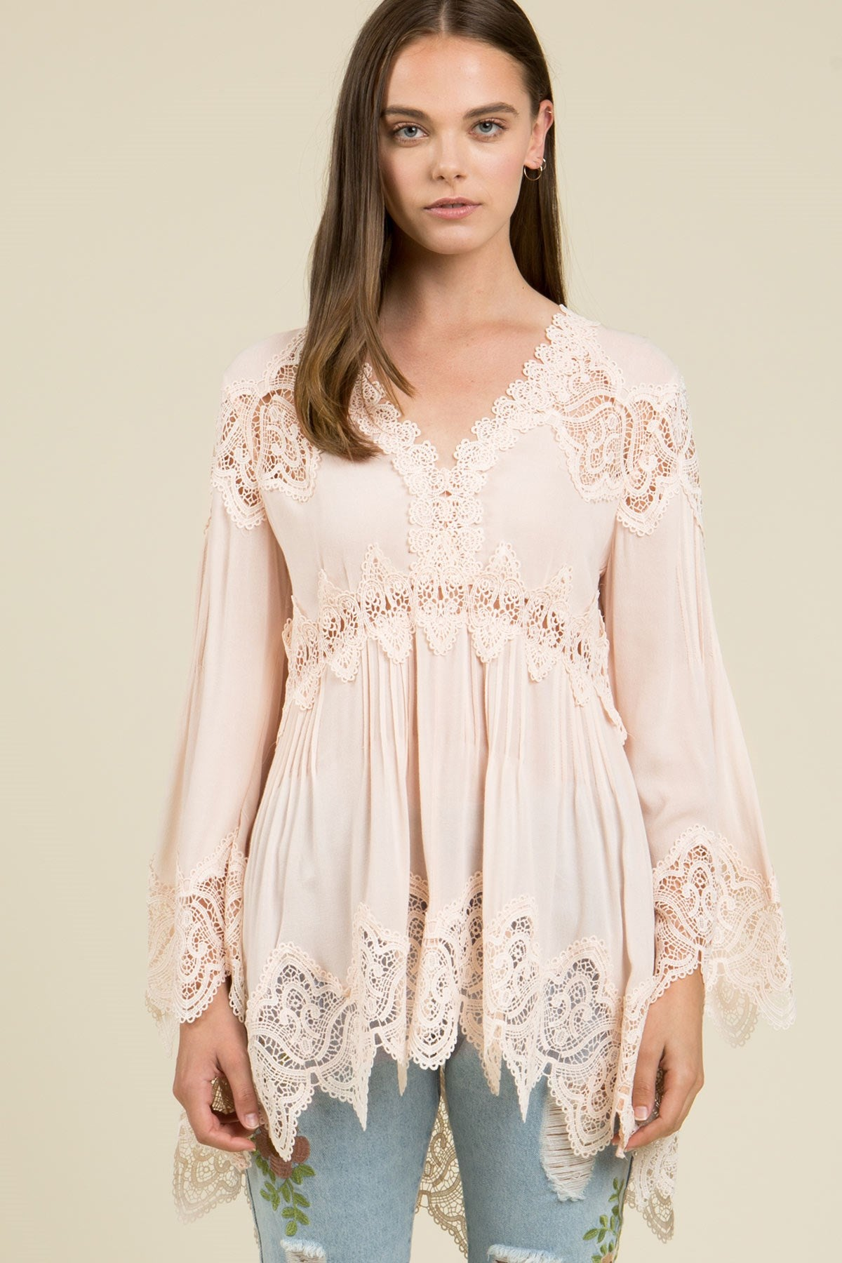 Front view young woman wearing pink empire waist lace trim tunic top
