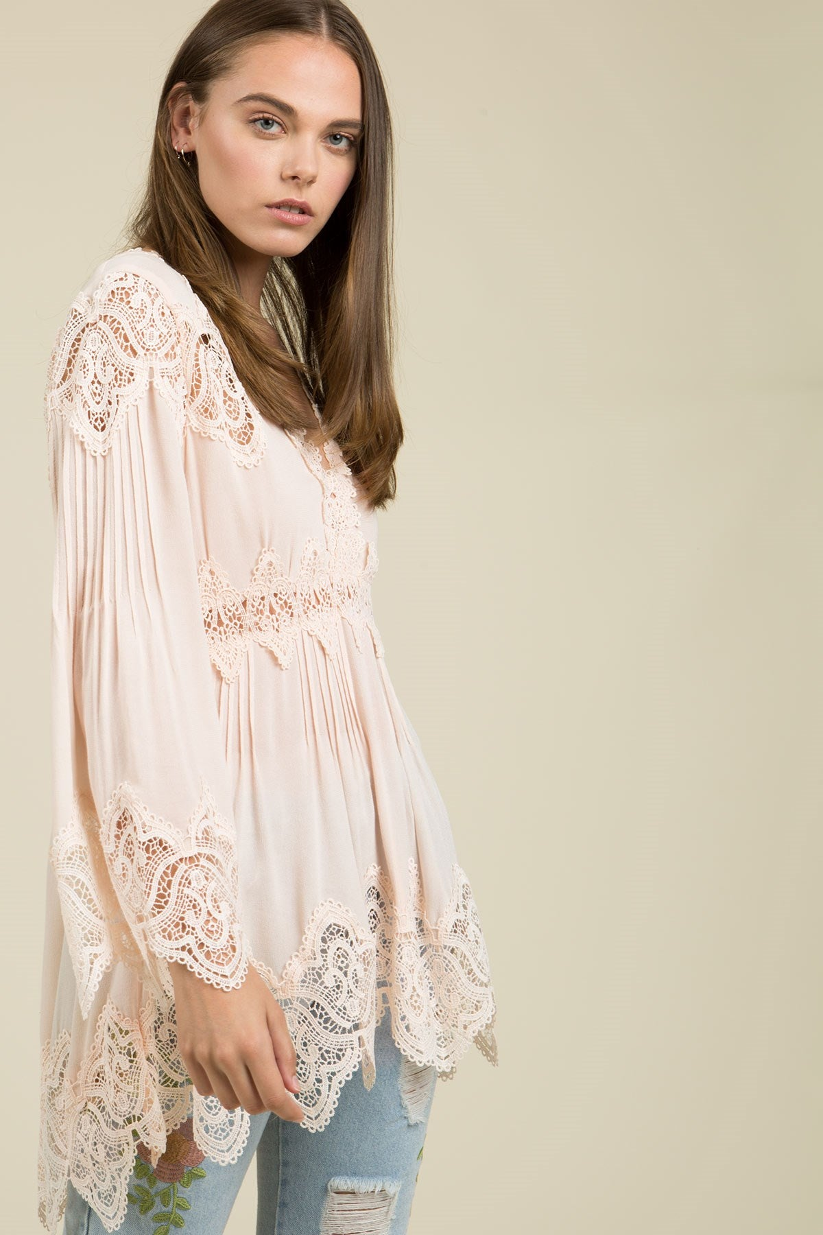 Side view young woman wearing pink empire waist lace trim tunic top