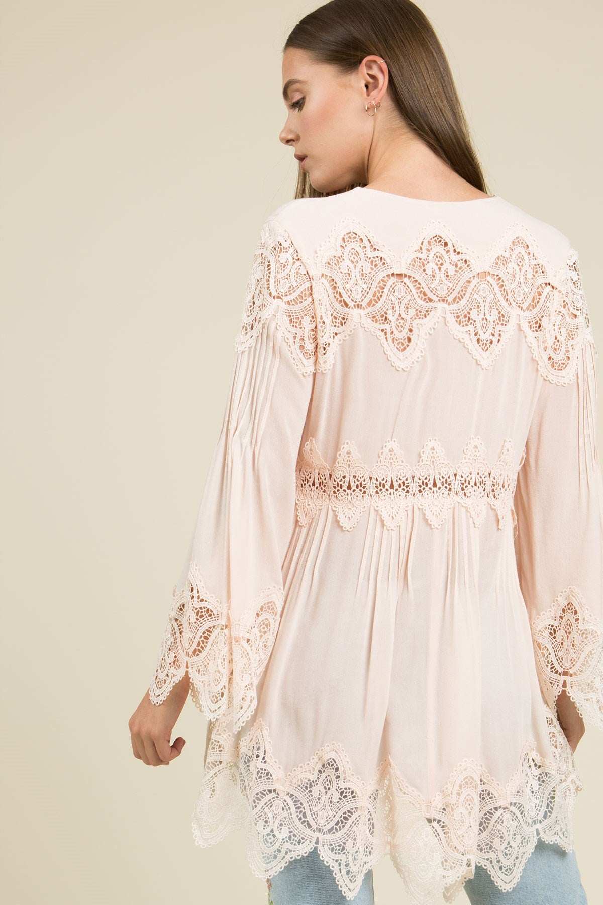 Back view young woman wearing pink empire waist lace trim tunic top
