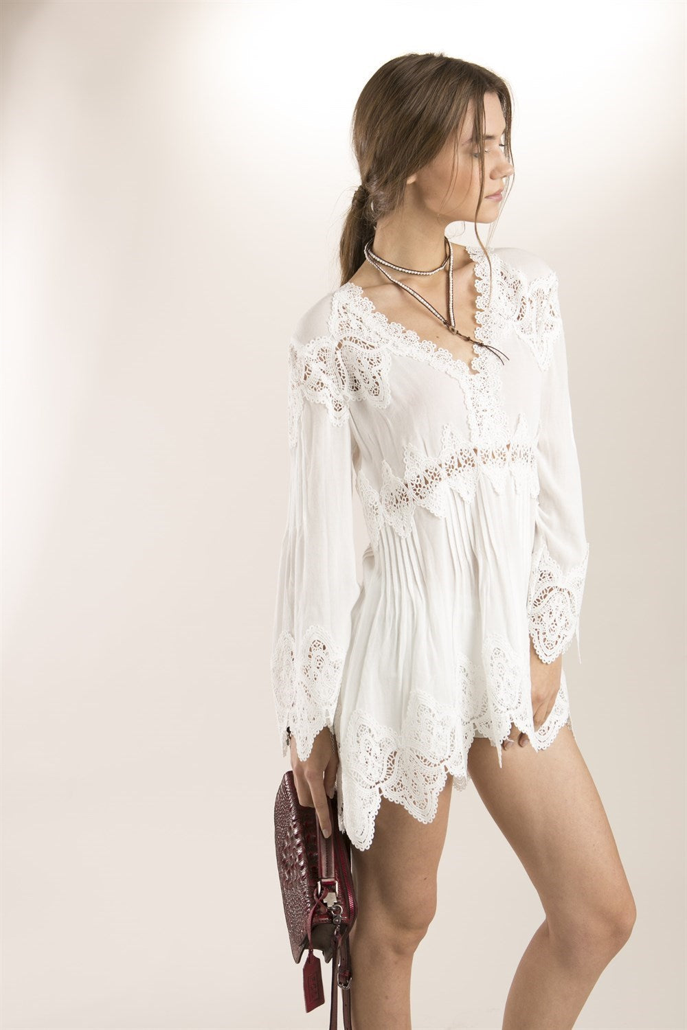 Right side view young woman wearing white empire waist lace trim high-low tunic top