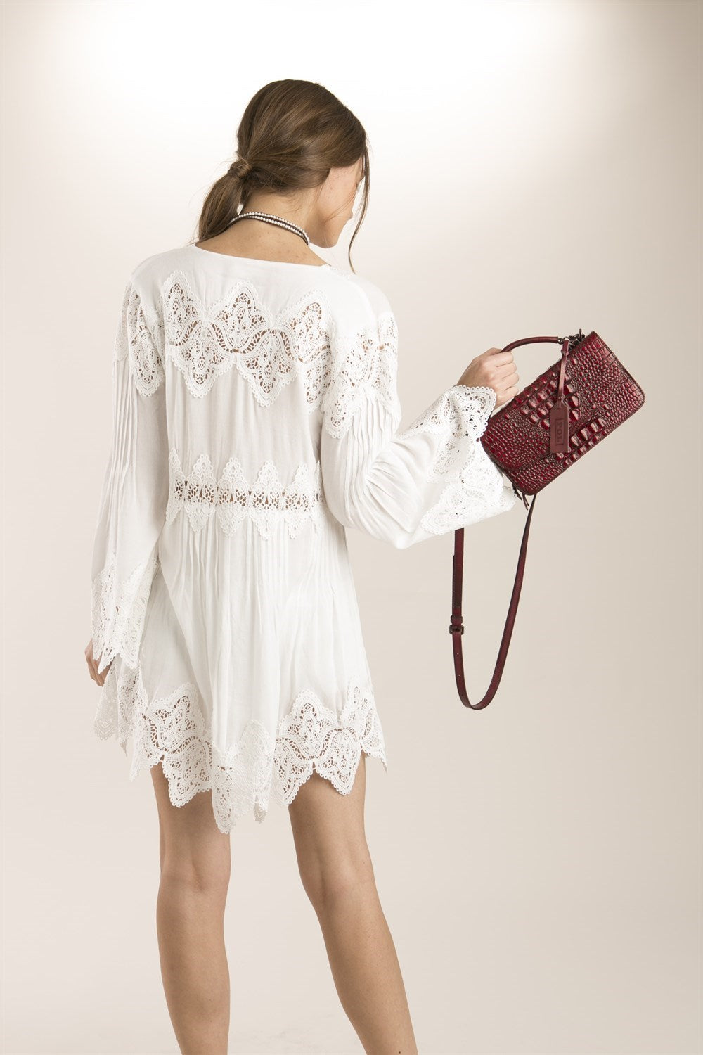 Back view young woman wearing white empire waist lace trim high-low tunic top