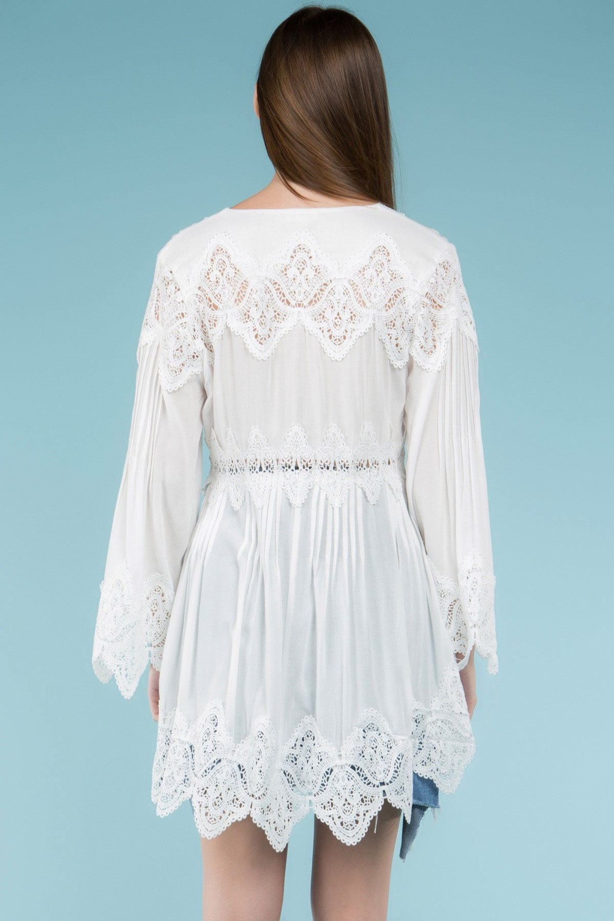 Back view young woman wearing white empire waist lace trim tunic top