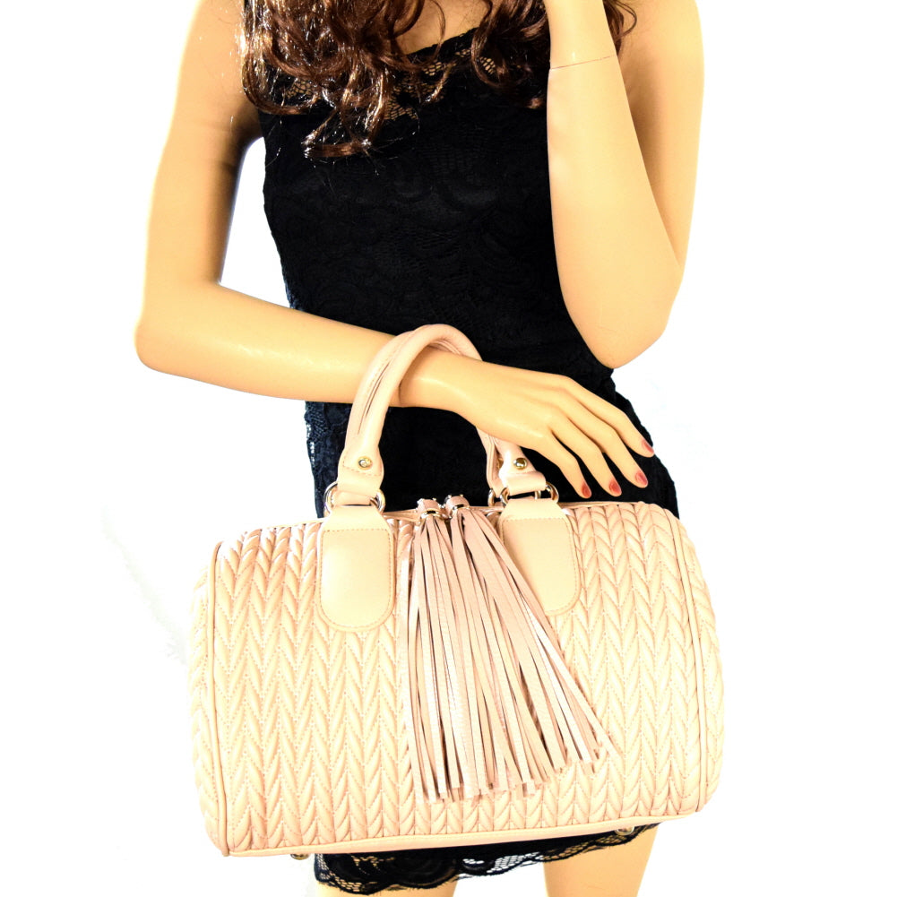 Woman holding light pink quilted satchel handbag with two long tassel accents in front of her
