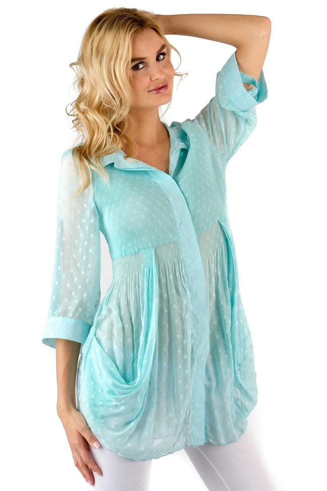 Front view woman wearing light turquoise dotted Swiss side drape tunic top with roll tab sleeves