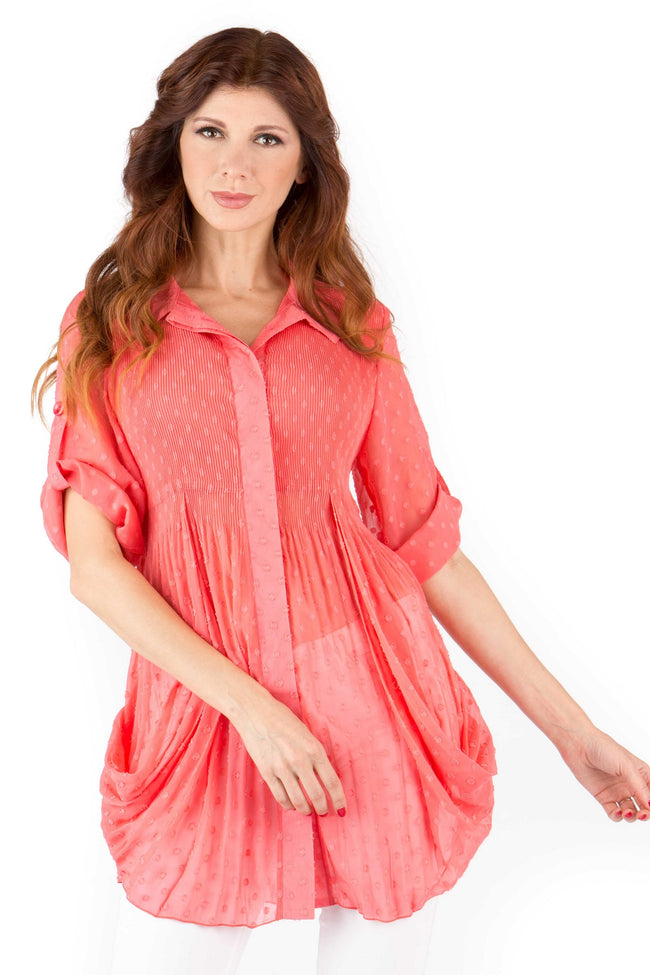 Front view woman wearing light coral dotted Swiss side drape tunic top with roll tab sleeves