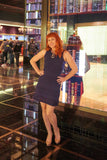 Full view woman wearing navy knit fit and flare dress in Cosmopolitan Hotel in Las Vegas