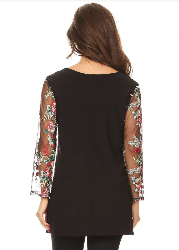 Back view plus size woman wearing black tunic top with sheer sleeves with floral embroidery