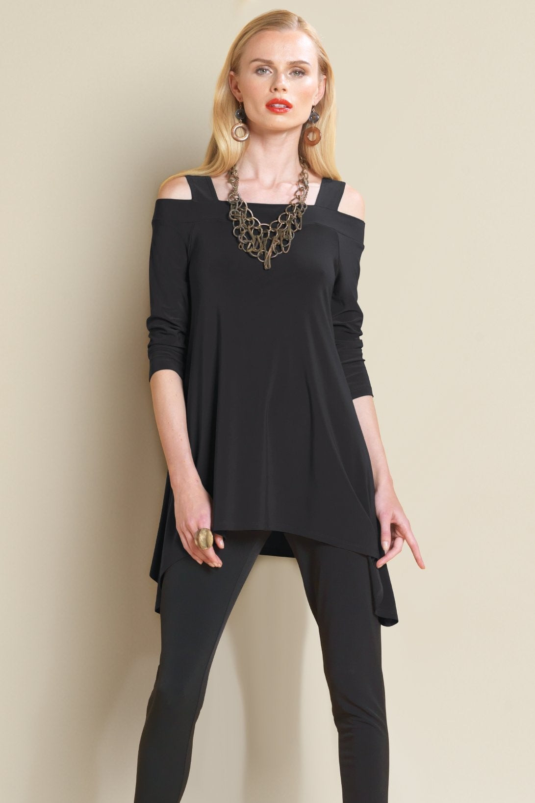 Front view woman wearing black cold shoulder tunic top and chunky necklace