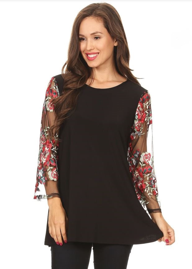 Front view plus size woman wearing black tunic top with sheer sleeves with floral embroidery