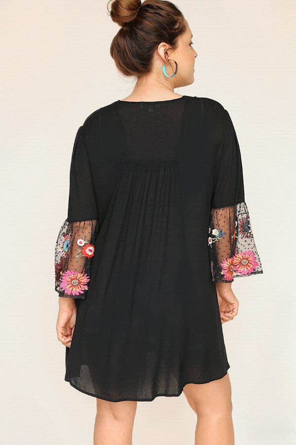 Back view young woman wearing black empire waist sheer sleeve dress