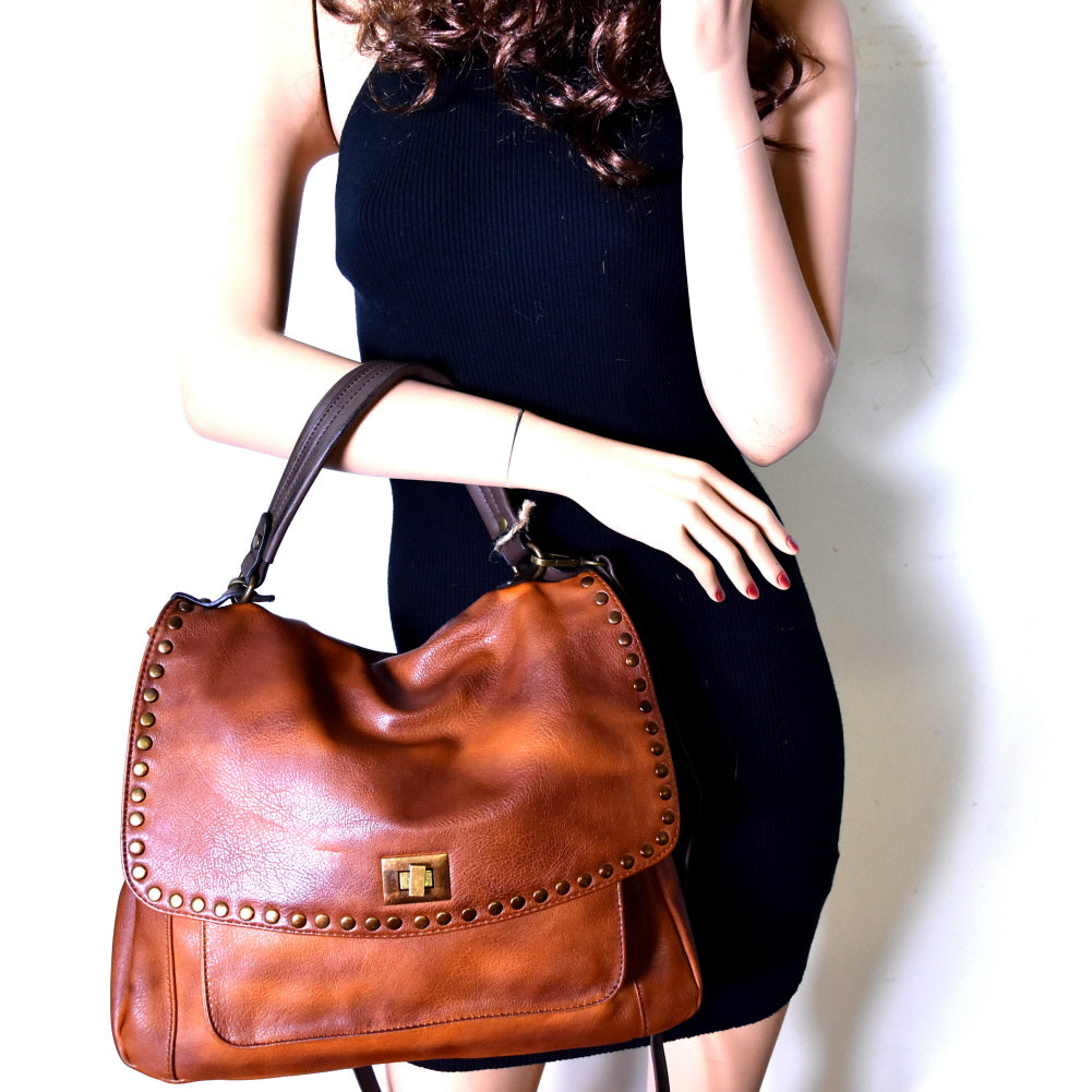Front view woman holding brown vegan leather foldover flap satchel with stud trim