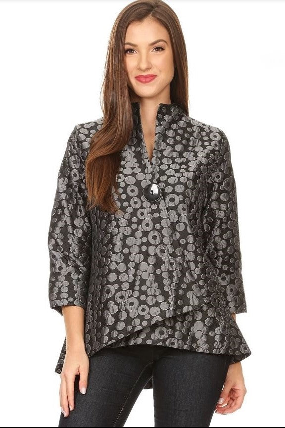 Front view woman wearing asymmetrical grey circle jacquard jacket with black button closure