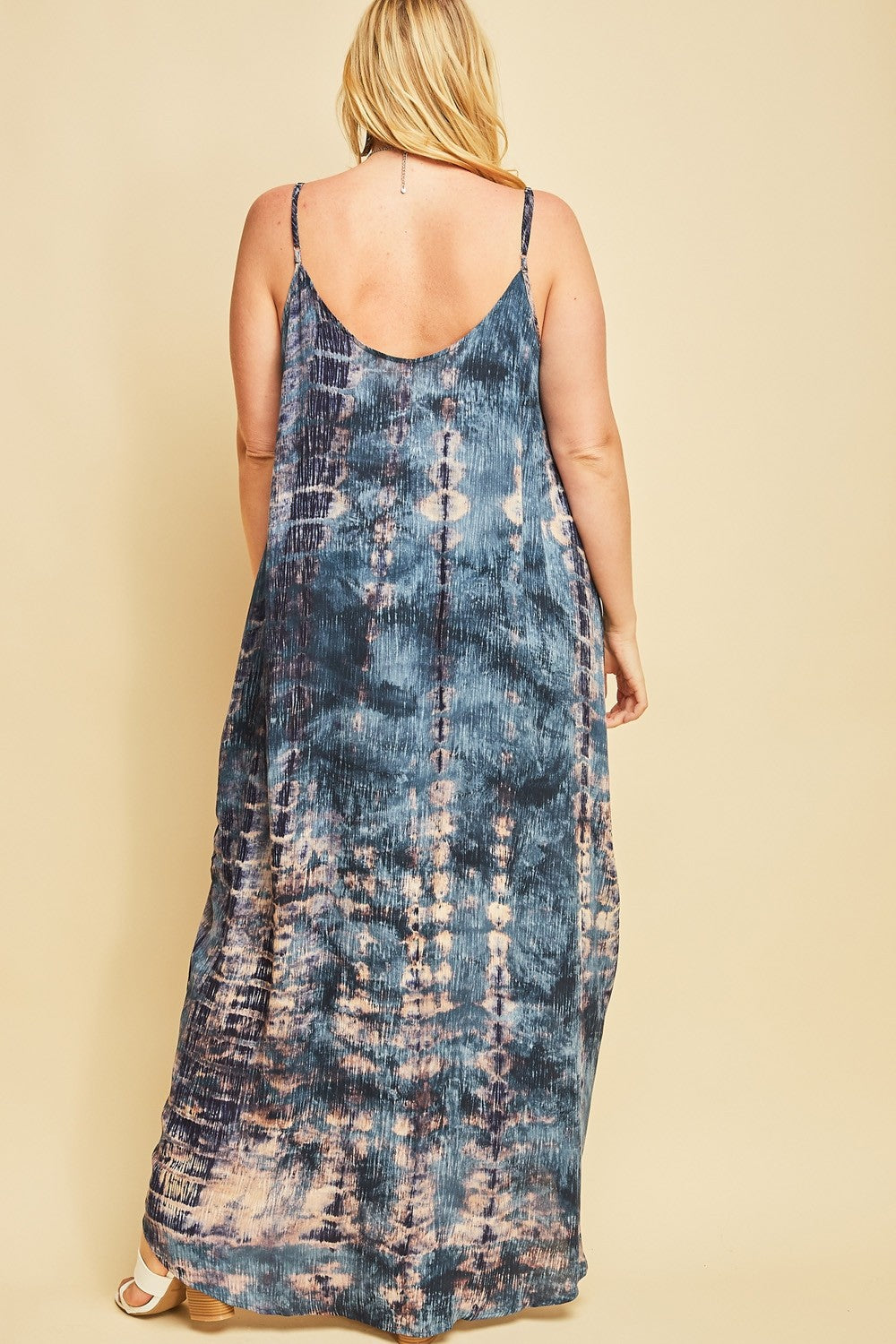 Back view plus size woman wearing sleeveless teal multi maxi dress with side pockets