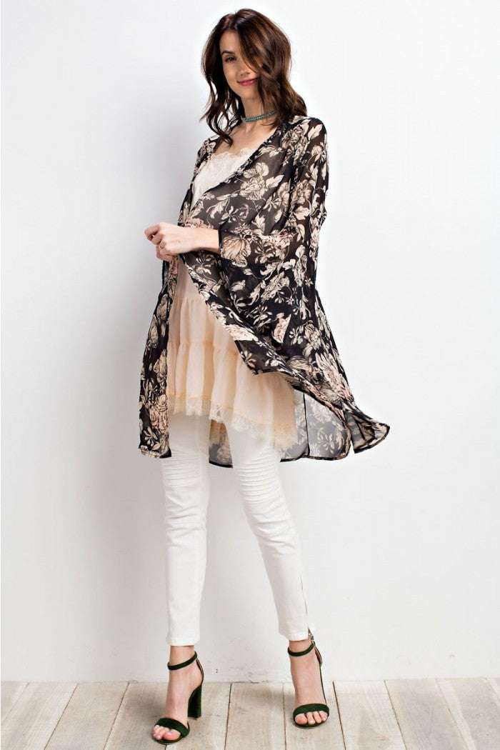 Full view woman wearing black/ivory floral print woven kimono cardigan with dramatic bell sleeves