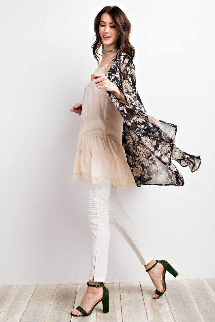 Full side view woman wearing black/ivory floral print woven kimono cardigan with bell sleeves
